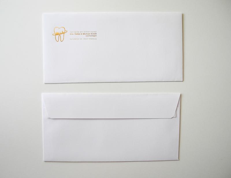 biała koperta z złotymi napisami